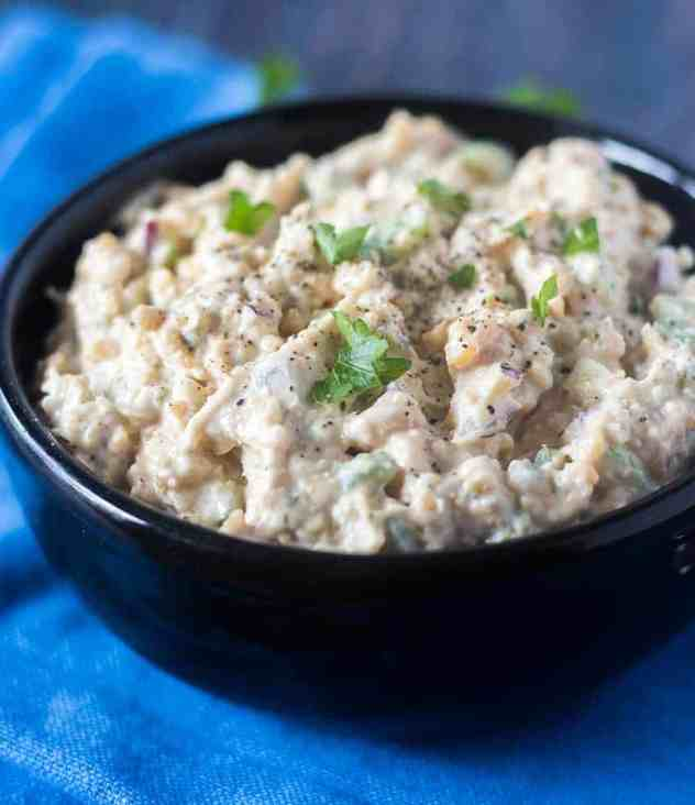 Mock Tuna Chickpea Salad in a black bowl topped with parsley and a blue napkin beside it.
