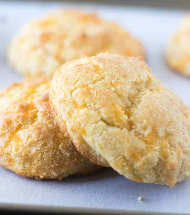 Three Garlic Cheddar Biscuits on a pan with parchment paper