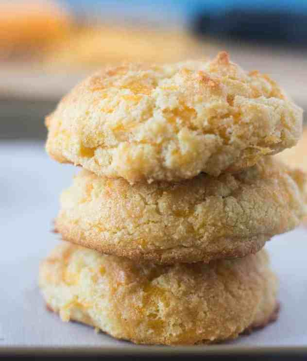 Three Cheddar Biscuits stacked on top of each other on a baking pan lined with parchment paper.