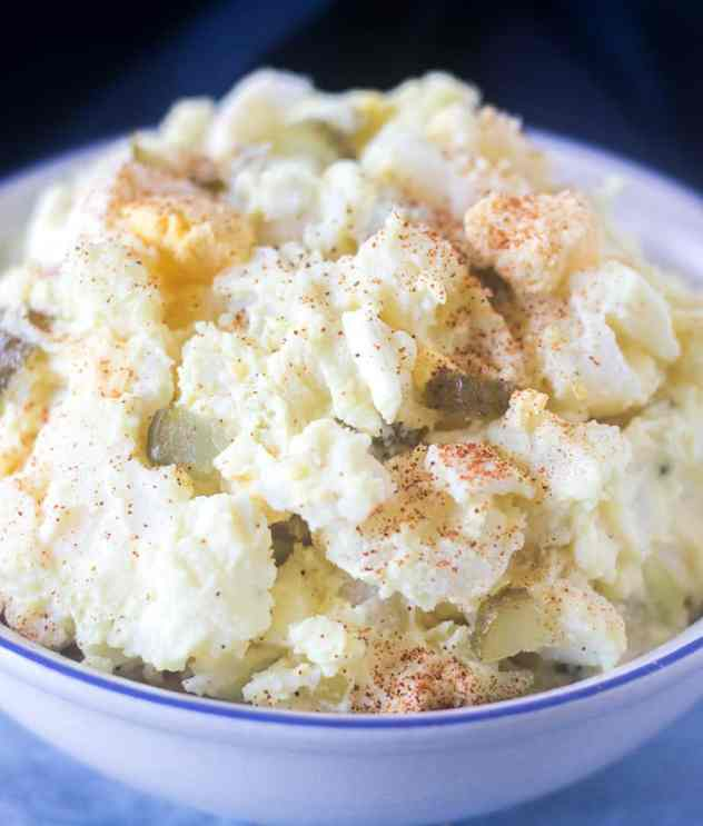 Mustard Potato Salad in a white bowl sprinkled with paprika.