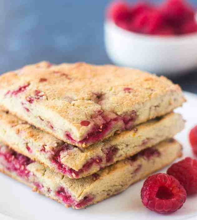 Raspberry Scones stacked on a white plate with fresh raspberries beside them.