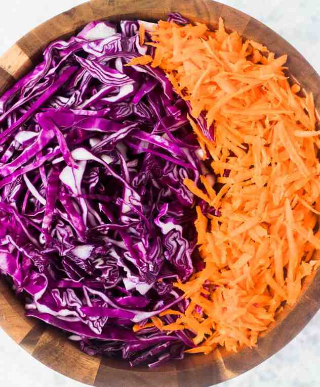 Shredded red cabbage and carrots in a wooden salad bowl.