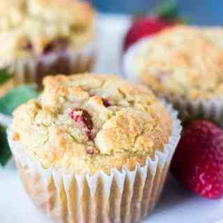 Strawberry Muffins on a white plate with fresh strawberries.