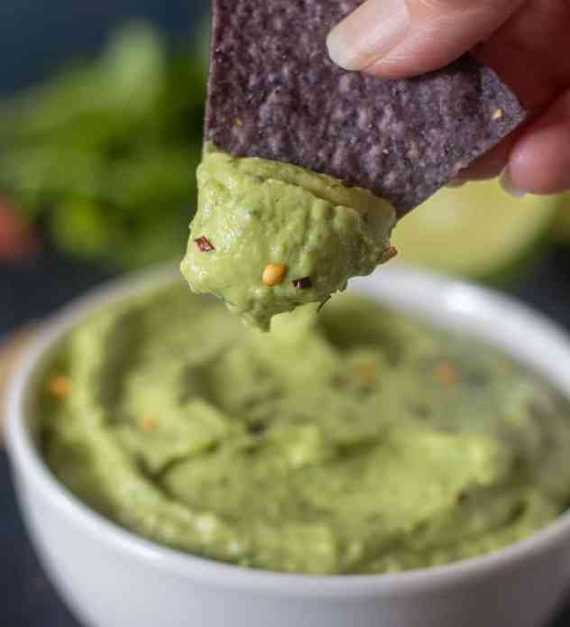 Avocado dip on a tortilla chip.