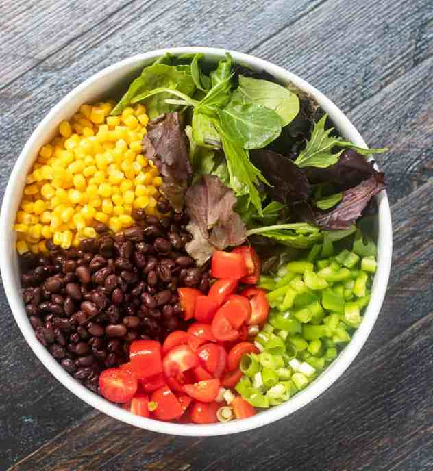 Lettuce, corn, black beans, grape tomatoes, green onions, bell pepper in a bowl.