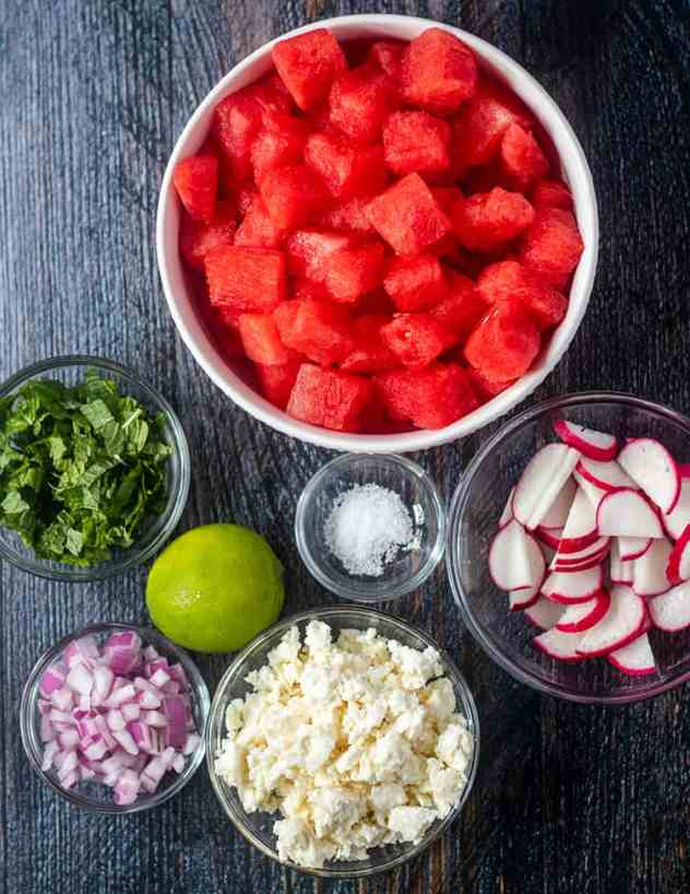 Watermelon cubes, mint leaves, lime red onion, salt, feta cheese, sliced radishes.