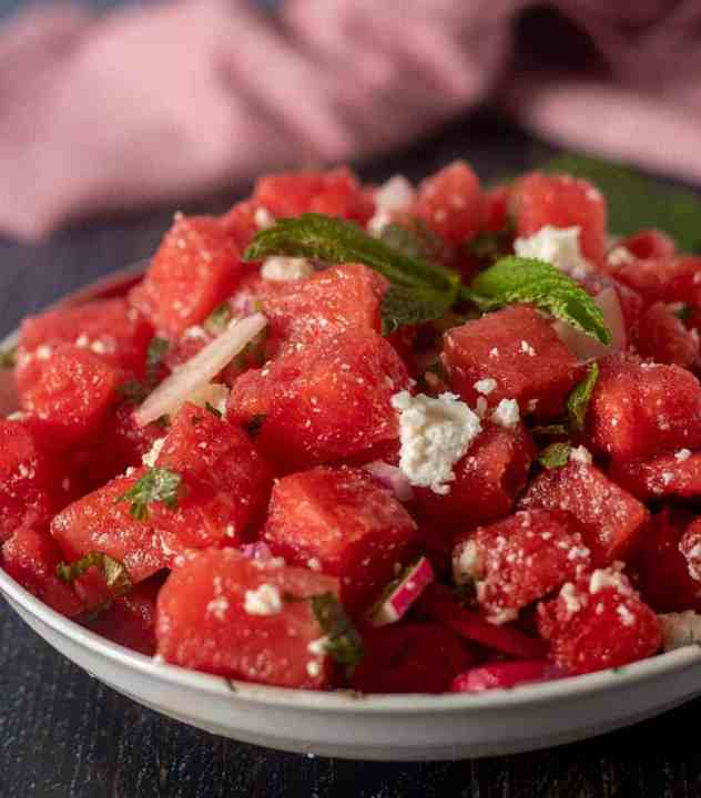 Watermelon Feta Mint Salad in a white bowl garnished with fresh mint leaves.