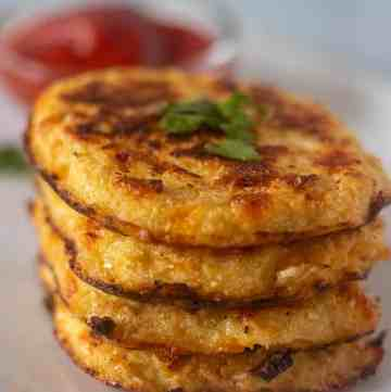 Cauliflower Hash Browns stacked on a plate with ketchup in a bowl.