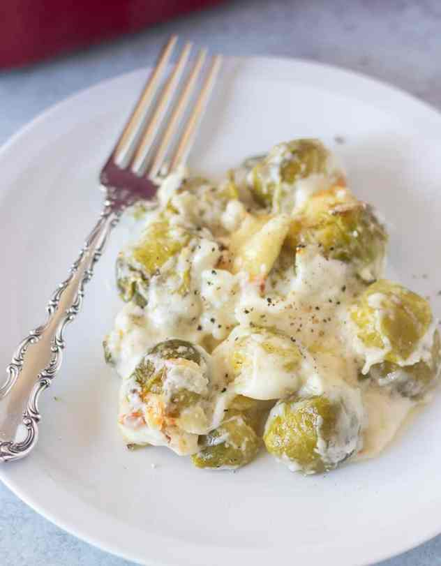 brussel sprouts au gratin on a white plate with a silver fork.