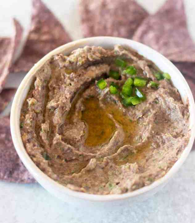 Black Bean Hummus in a white bowl topped with olive oil and jalapeños