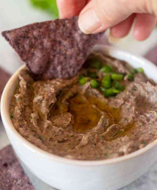 Black Bean hummus being dipped with a tortilla chip