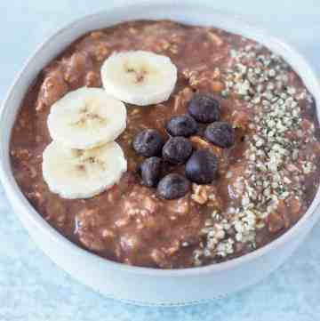 Chocolate Overnight Oats topped with banana slices, dark chocolate chips, and hemp seeds.
