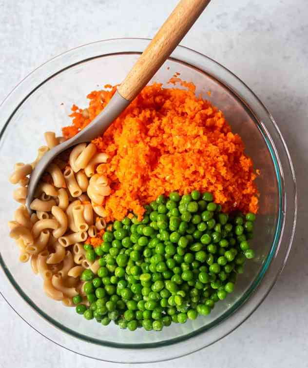 cooked elbow noodles, carrots and peas in mixing bowl