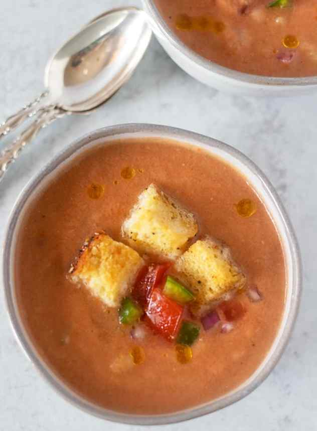 gazpacho soup in a bowl topped with croutons and extra chopped vegetables