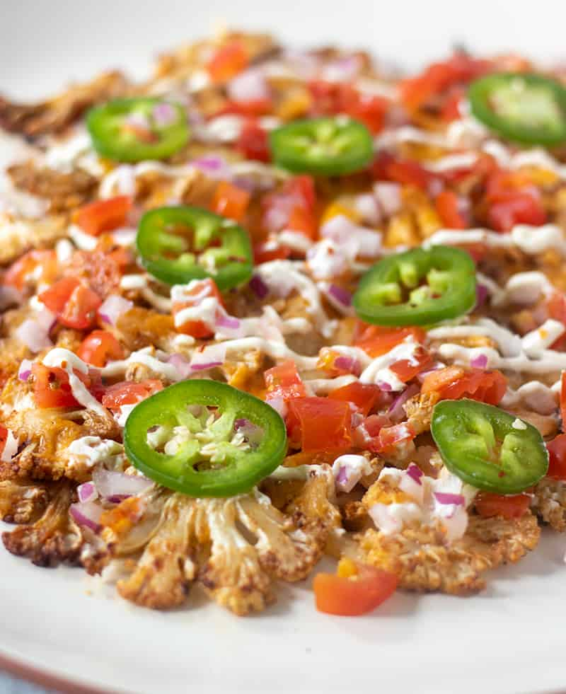 Cauliflower nachos topped with tomatoes, jalapeno, cheese
