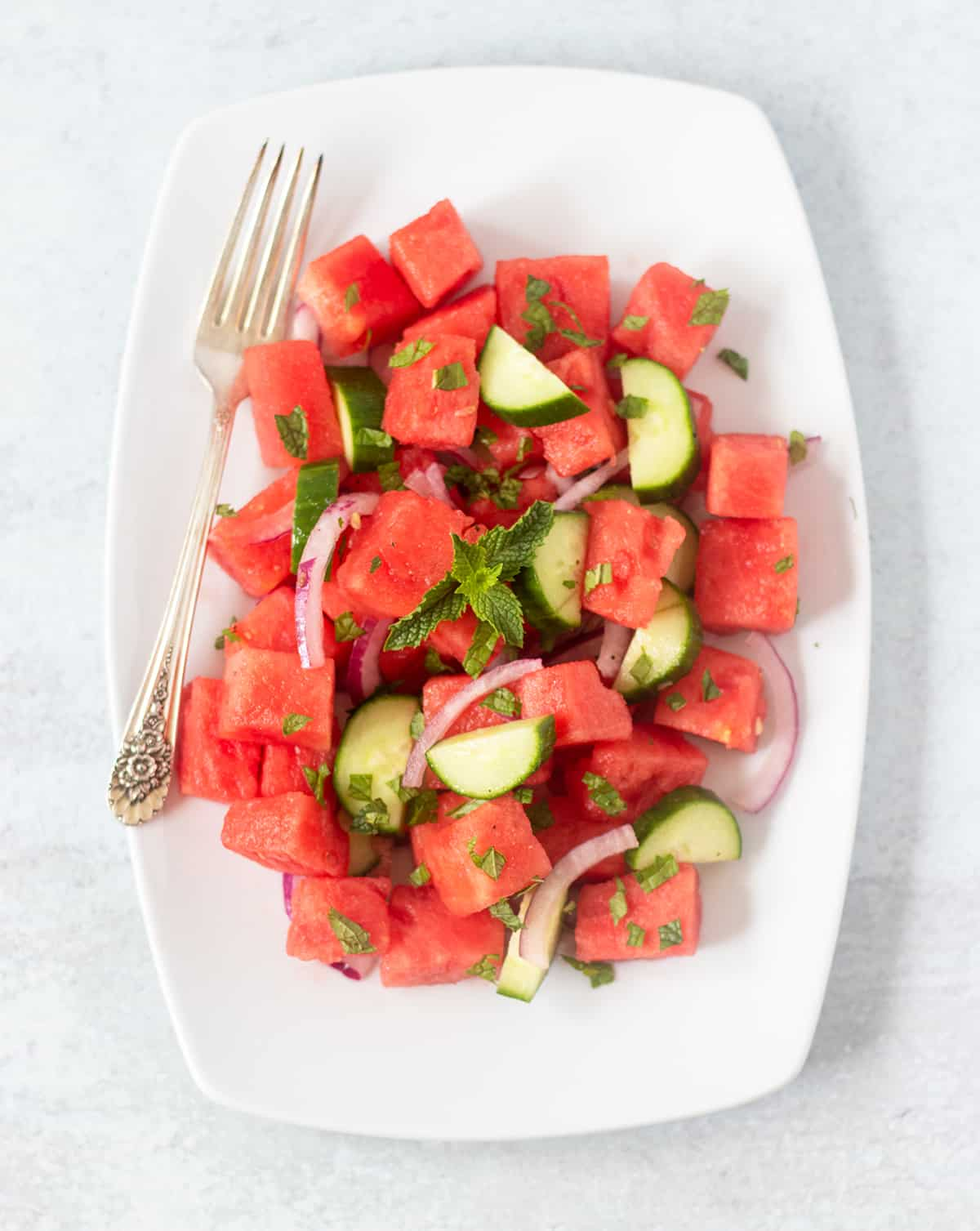 Watermelon Cucumber Salad on a white serving platter with a silver fork