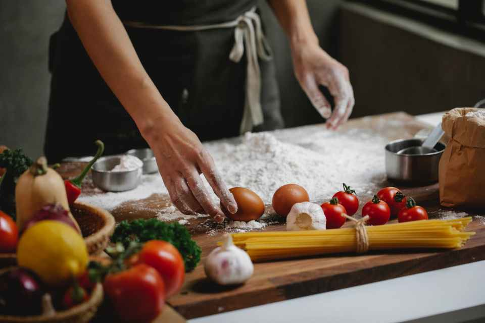 cook preparing food dish standing at table with different ingredients