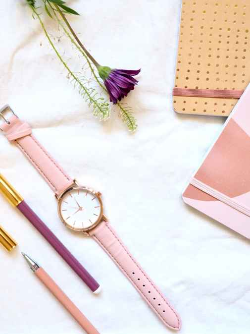 flat lay photography of watch near pens and notebook