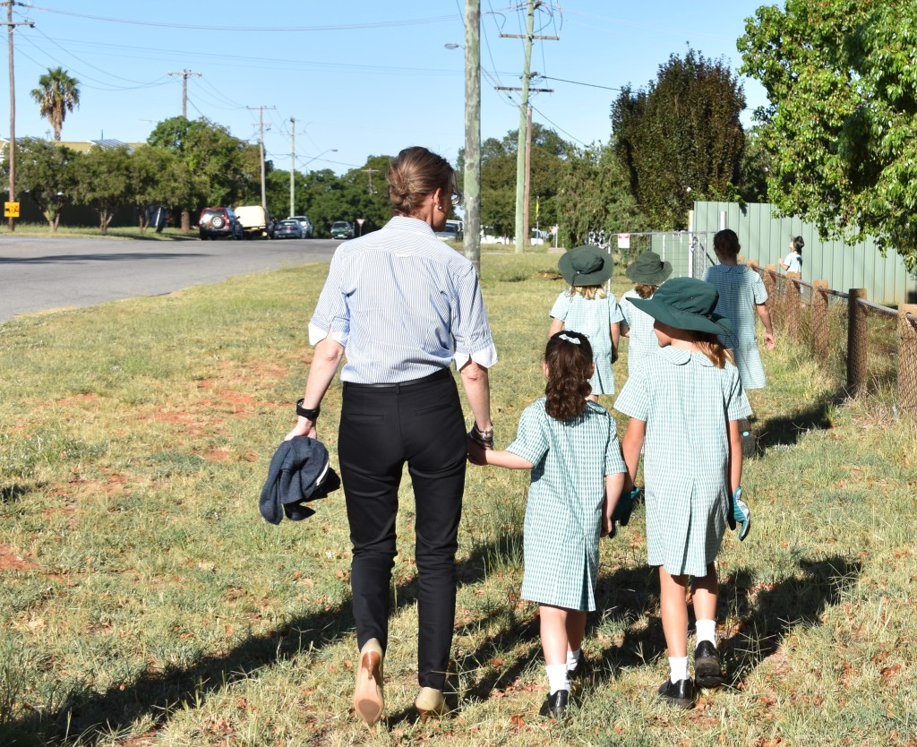 Steph Cooke walks with primary school students through grass.