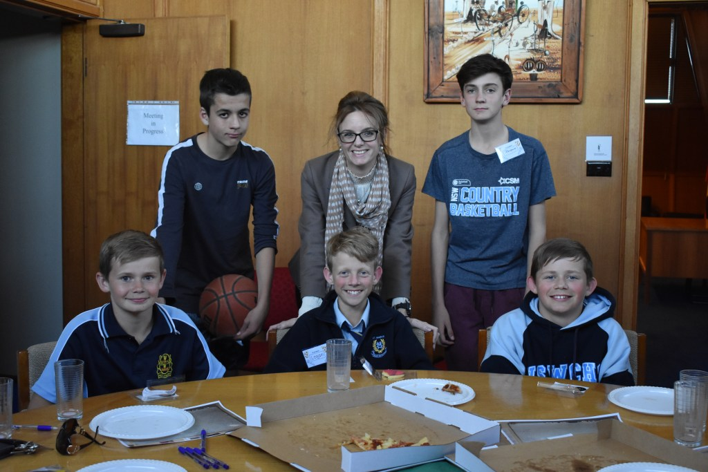 Five young boys surround Steph Cooke at the Pizza and Pitch event in West Wyalong