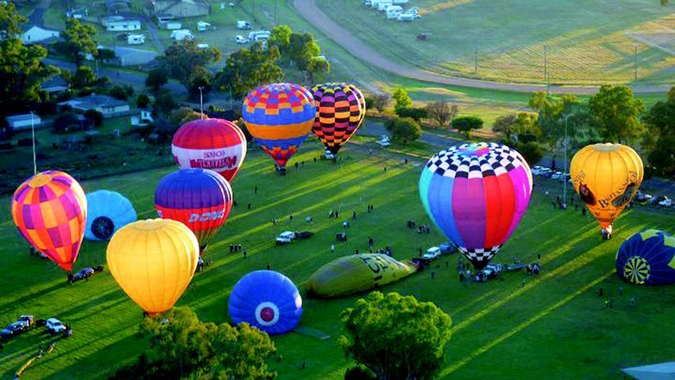 Brightly coloured hot air balloons on a green field.