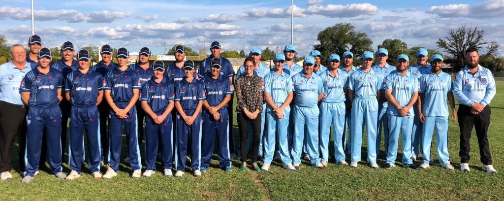 Two teams of 12 cricketers surround Steph Cooke MP. The teams are dressed in light blue and navy.