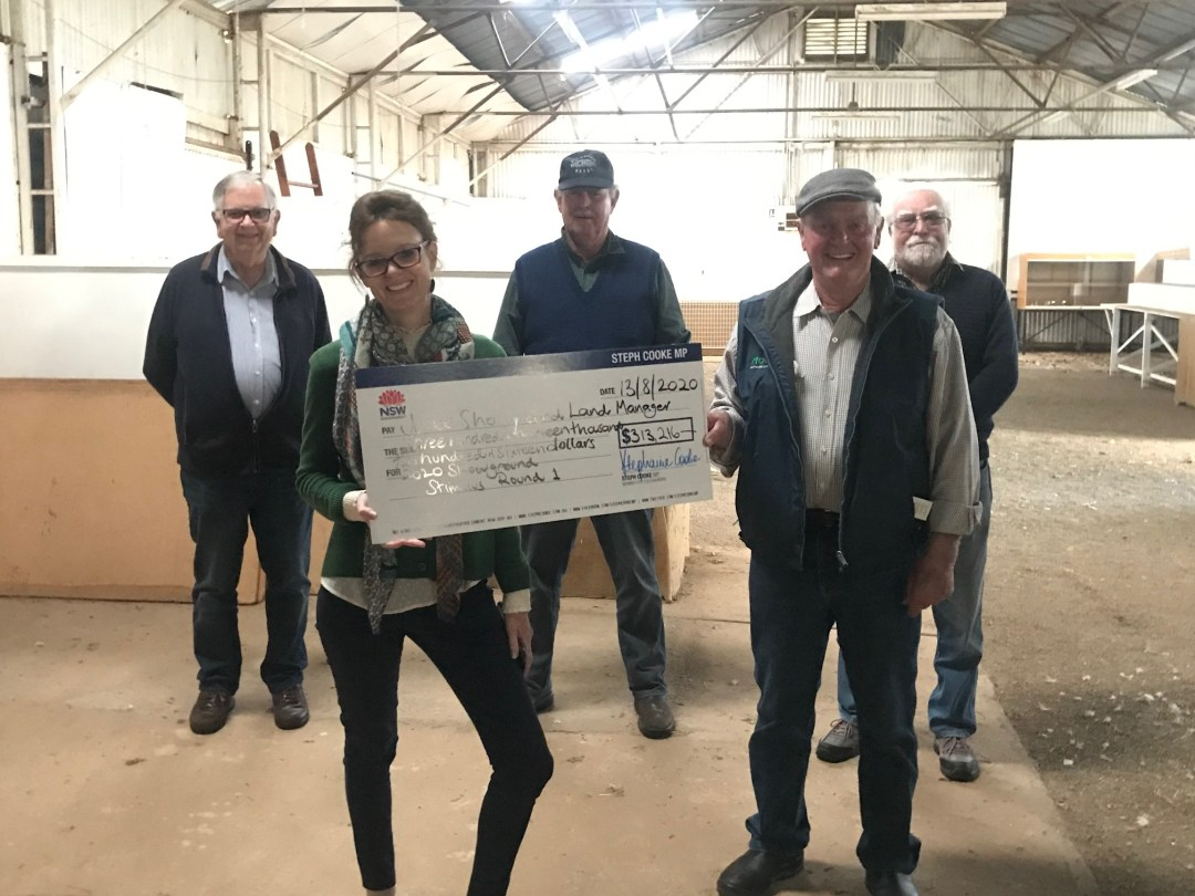 Pat Foley, Steph Cooke MP, Col Randall, Peter Commens and Phil Cummins stand in the Lord Pavilion. They hold a large cheque and smile at the camera.