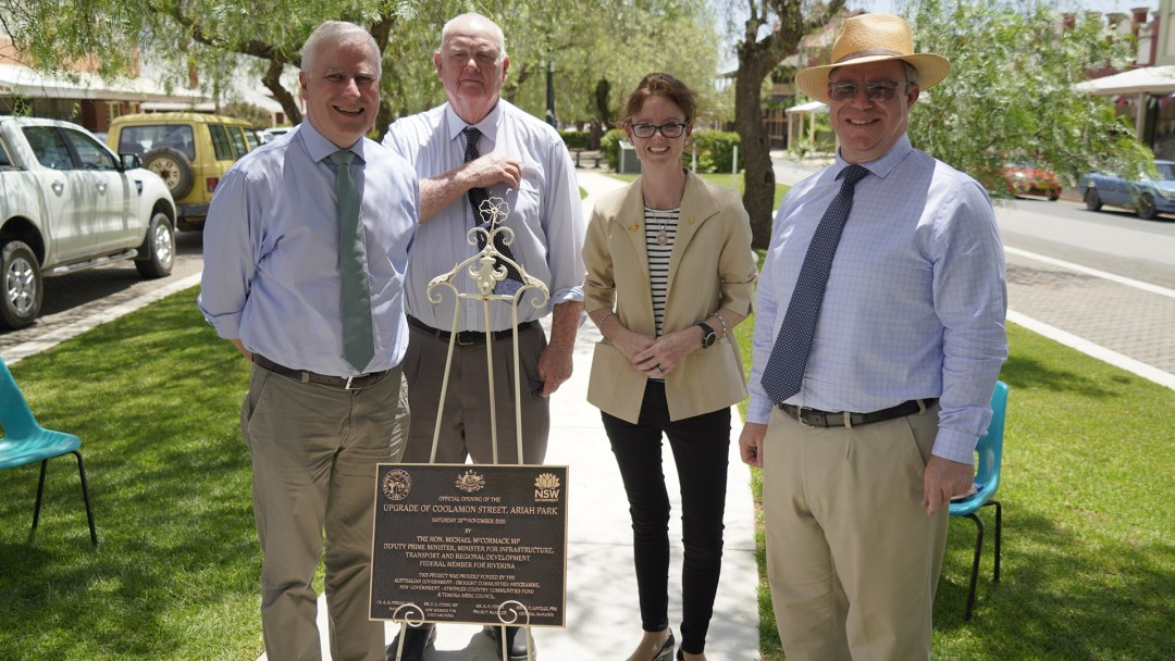 Michael McCormack, Nigel Judd, Steph Cooke and Rick Firman stand around a plaque which sits on an easel. Behind them is new grass and trees.