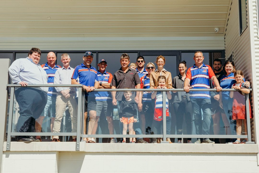 Steph Cooke stands with people in Young team jerseys on a balcony with a glass front.