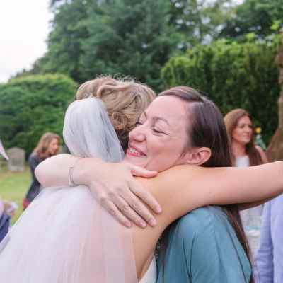 Norfolk wedding photographer – bride hugging guest