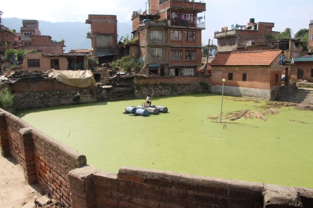 A boy making his own fun. The green stuff is algae covered water, a local water source for the town