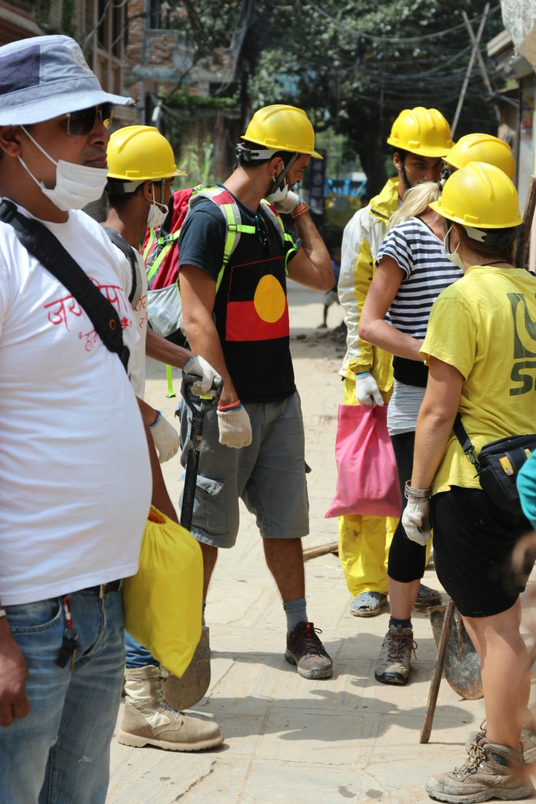 Volunteers from around the world, even Italians wearing distinguishable, to the author, designs on their shirts