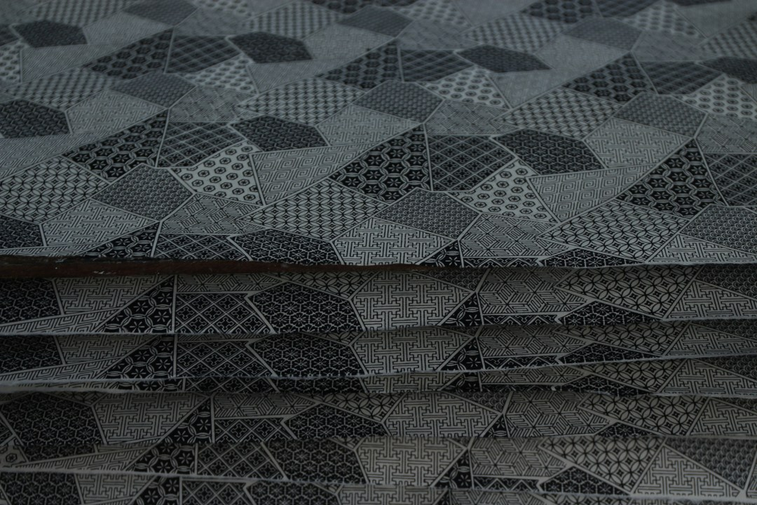 In yet another factory, a small shed, the paper is silk screened through various patterns