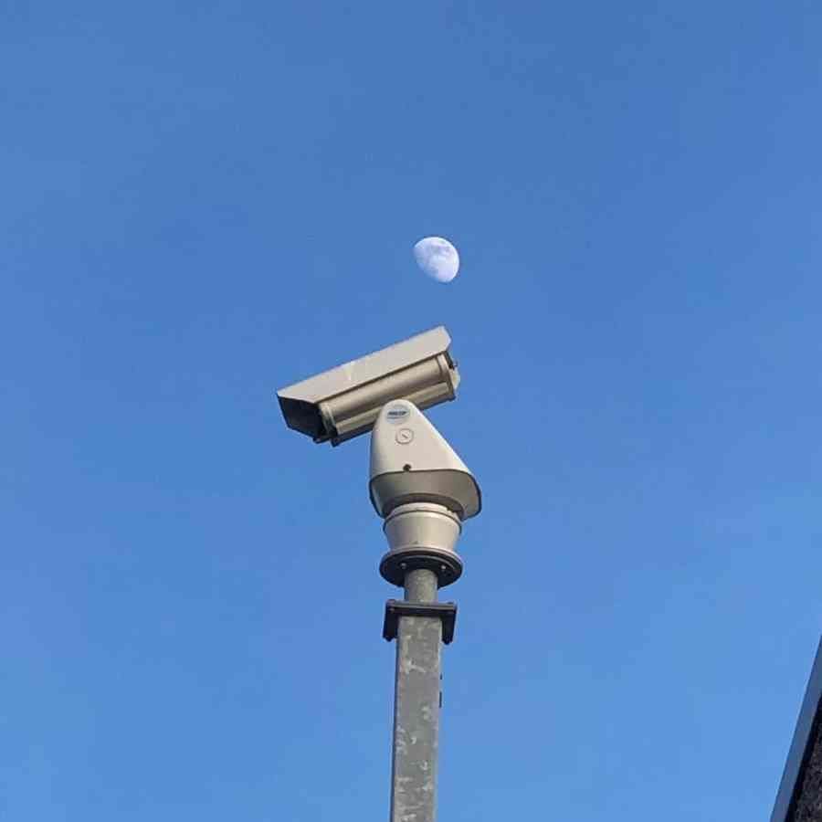 The moon above a surveillance camera
