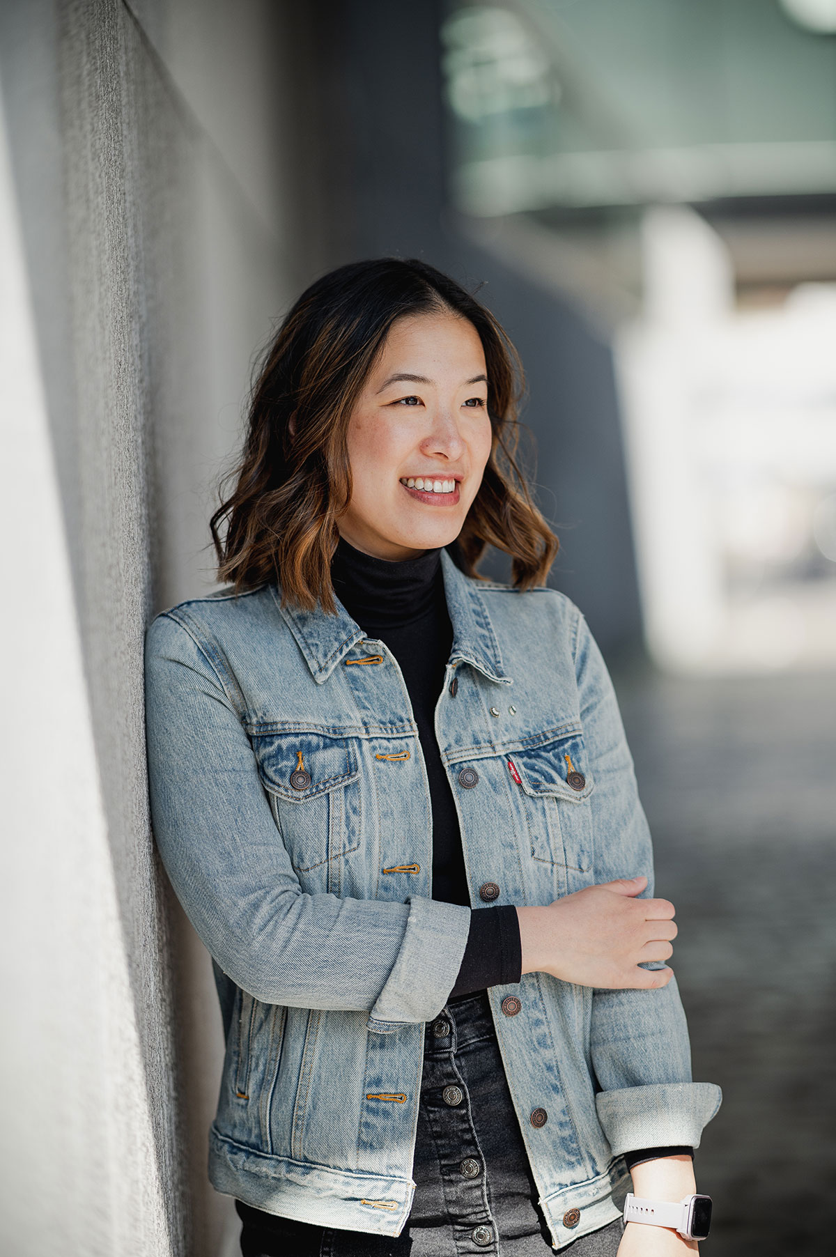 Woman in denim jacket leaning against wall