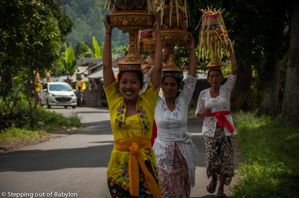 Women caring heavy offerings made form fruits at their head walking in the quiet streets of Kedisan