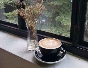 A black cup and saucer with a cappuccino sits on a ledge next to a window.