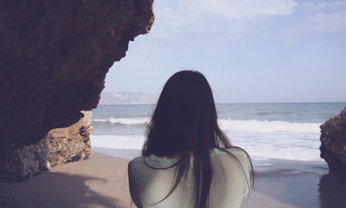We see the back of a woman looking out to the sea.