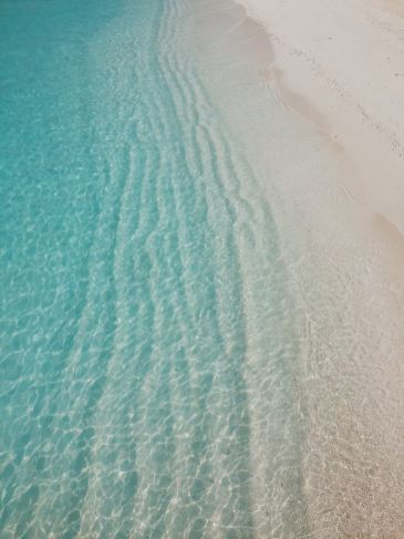 A crystal clear calm greenish sea rippling on the smooth sand.