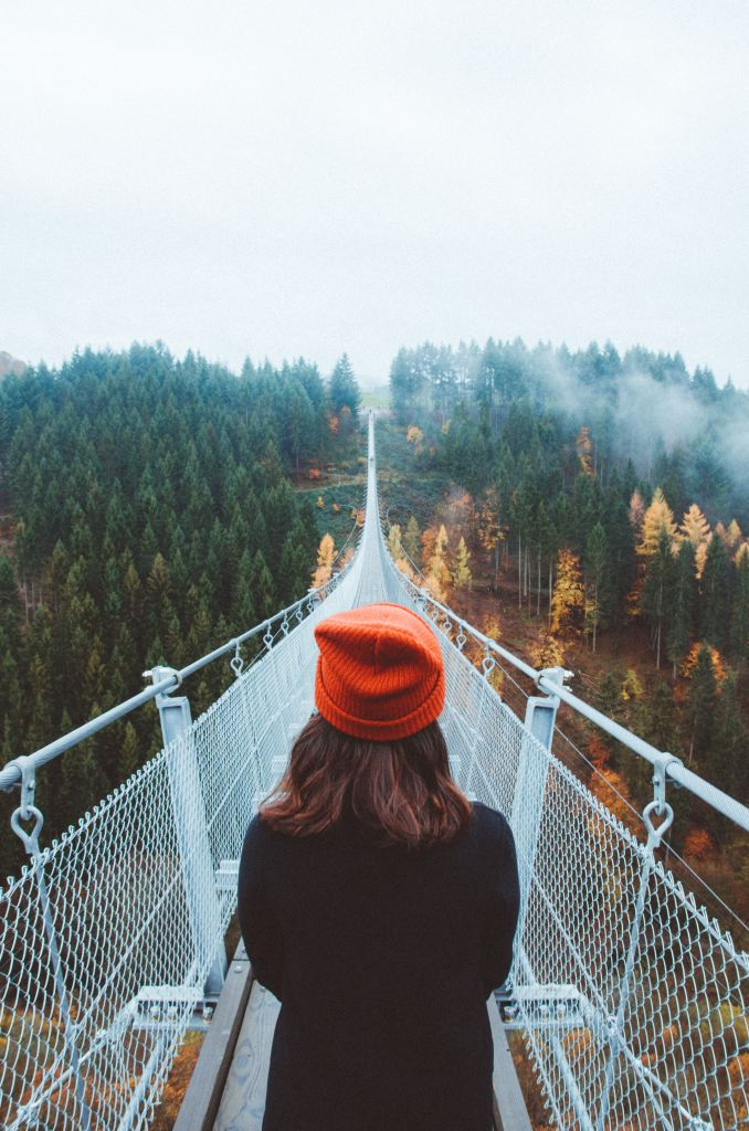 Woman looking ahead over a long foot bridge that extends over trees