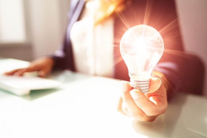 Close-up Of A Businesswoman's Hand Holding Illuminated Light Bulb In Office