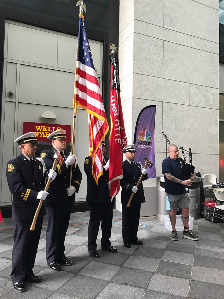 image of police officers holding flags and steve plying bagpipes