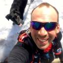 Man taking a photo in the snow with a dog