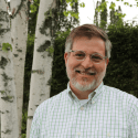 Photo of president Matthew Derr standing in front of a green hedge and a white birch tree