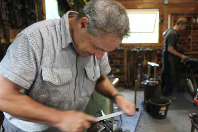 Filing down a handmade axe head in the blacksmithing class