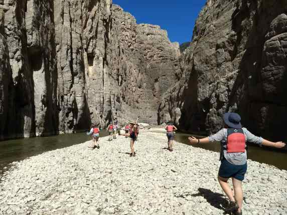 Group walking through the canyon on a rocky sand bar