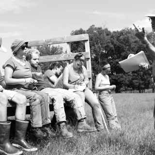 students sit on the back of a trailer on a sunny Kentucky day, listening and learning in the Wendell Berry Farming Prorgram