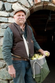Organic fruit grower Michael Phillips of Lost Nation Orchard stands at the foundation of the barn he built with a bucket full of GoldRush apples.