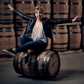 photo of Sas Stewart sitting on a barrel of her spirits