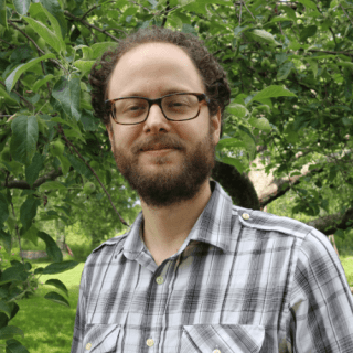 Michael Tessler '09 stands in front of a green apple tree in summertime